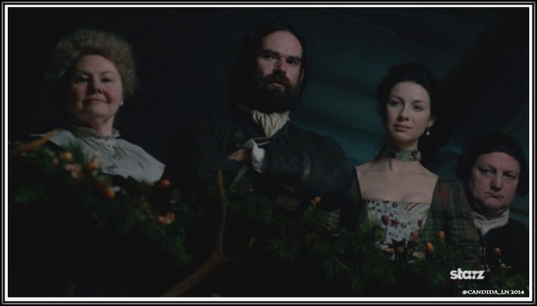 Mrs. FitzGibbons (Annette Badland), Murtagh Fizgibbons Fraser (Duncan Lacroix) and Claire Randall (Caitriona Balfe) watch Dougal MacKenzie make his vow to his elder brother, Colum.